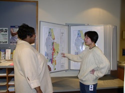 IS Analyst Chiaki Sakuma showing Permit Technician Zee Young some GIS maps.